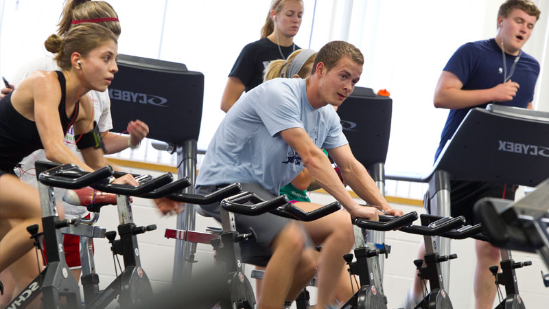 UE students riding exercise bikes and on treadmills in the Fitness Center.